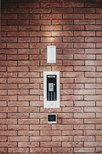 An emergency intercom and light on a brick wall of a building
