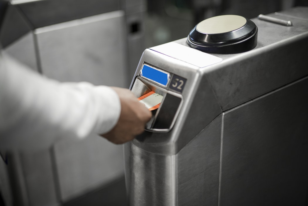 A hand using a card to activate a waist-high security turnstile