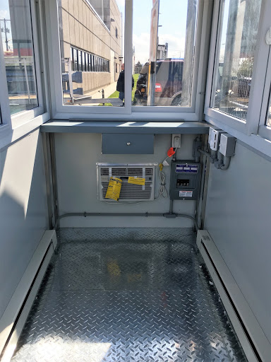 Interior of a prefabricated guard shack with a built-in AC unit, electrical and sliding windows.