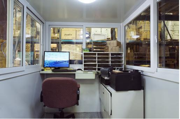 Interior of a prfabricated guard shack turned into a working station with desk and chair.