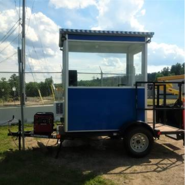A blue trailer guard booth at a construction site