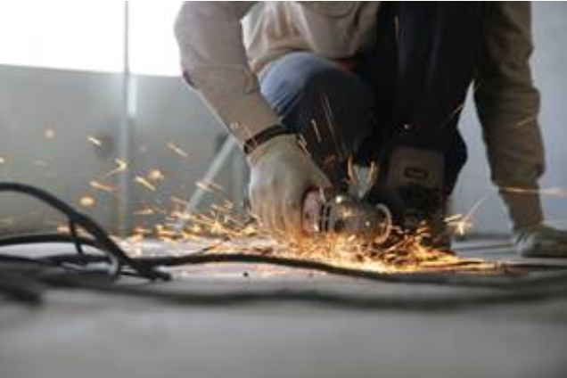 A construction worker using a power saw and making sparks