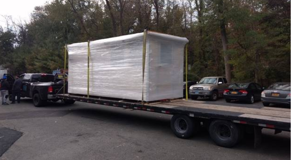 A small prefabricated building wrapped up on a flatbed trailer.