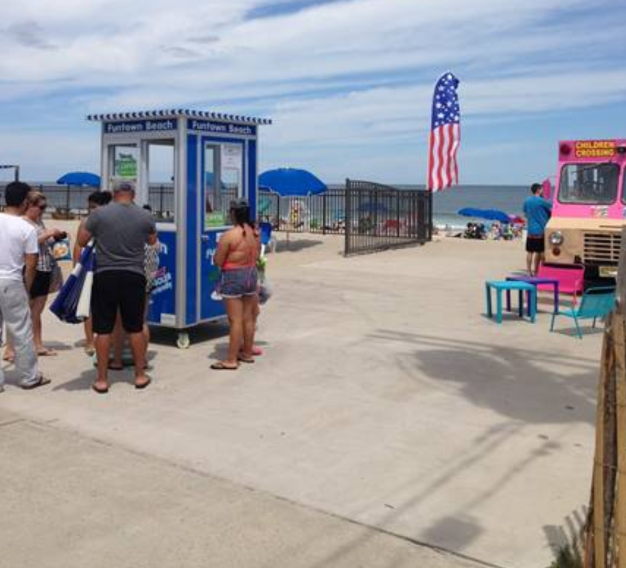 People standing around a blue booth at a beach
