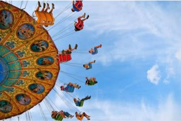 People riding a circular sky swing attraction at an amusement park - Maximize Profits in Amusement Park Management Systems