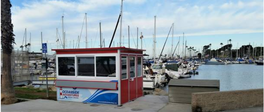 Red ticket booth design with Oceanside logo in front of marina