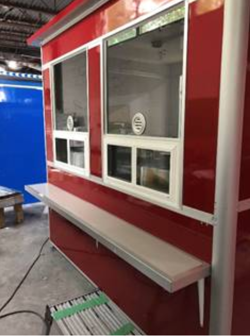 Red ticket booth with window speaker and customer counter.