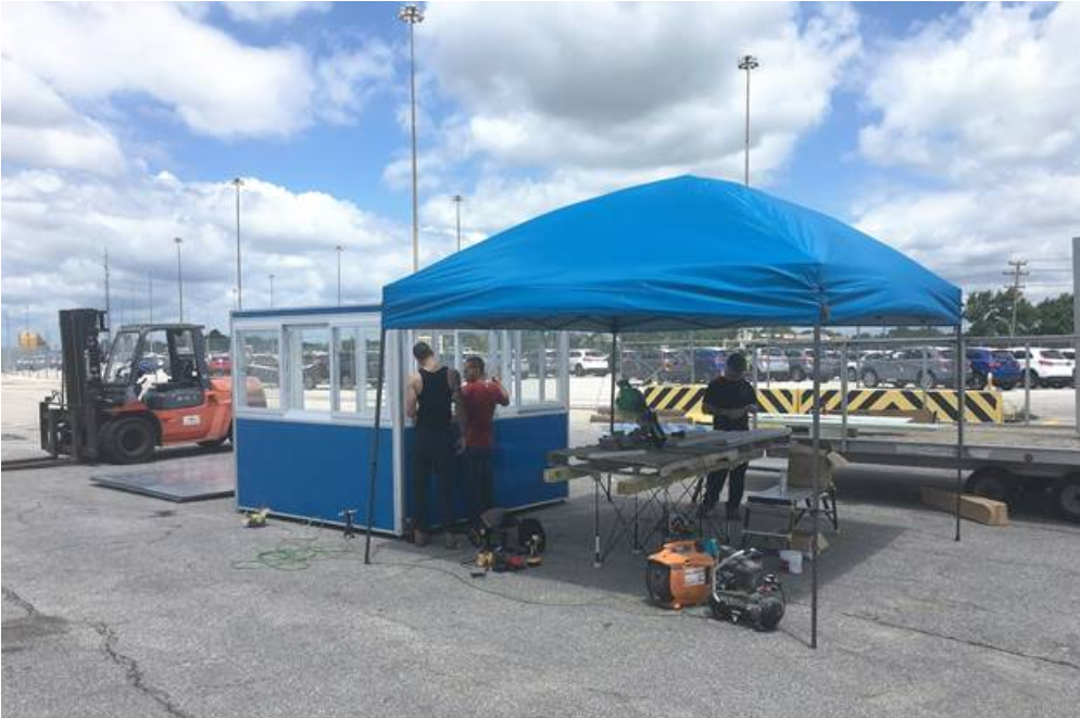 Workers assembling a blue guard booth in a parking lot.