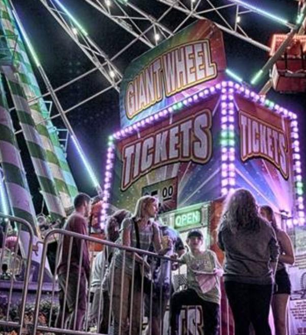 A neon lit ticket booth at an amusement park
