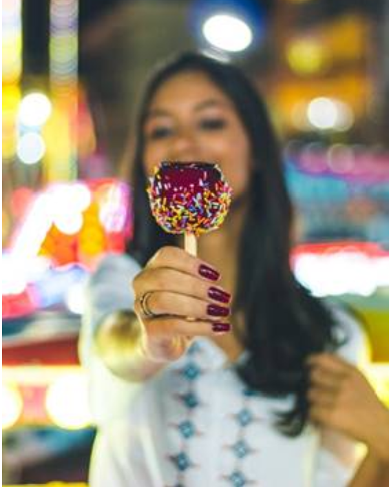 A girl holding a sprinkle coated candy apple at an affair.