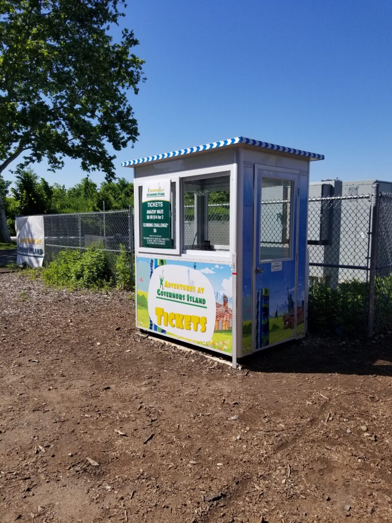 4x6 Ticket Booth in Governor's Island, NY on Festival Grounds with Perimeter Security Fencing, Swing Door, and Sliding Windows