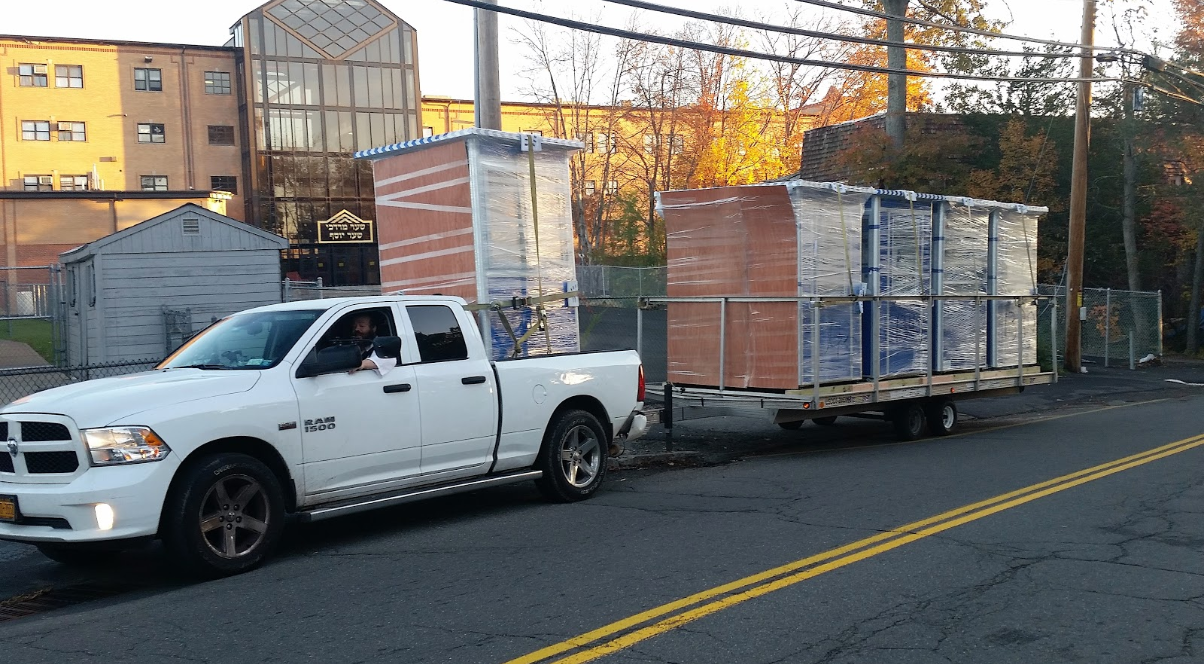 Shrink wrapped blue ticket booths being towed by a truck
