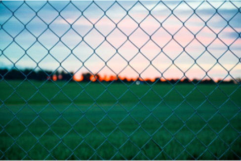 A chain link fence in front of a farm