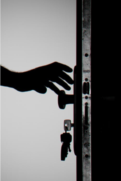 A hand reaching for a locked door with a key in it