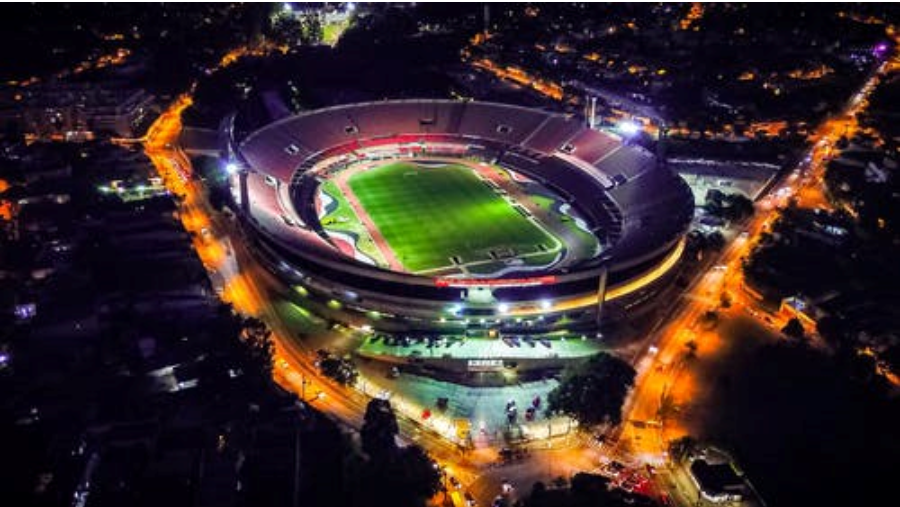 A large stadium lit up at night, as seen from above