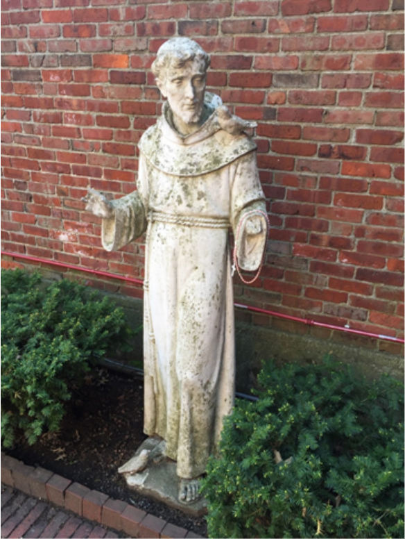 A religious statue of a man in front of a brick wall