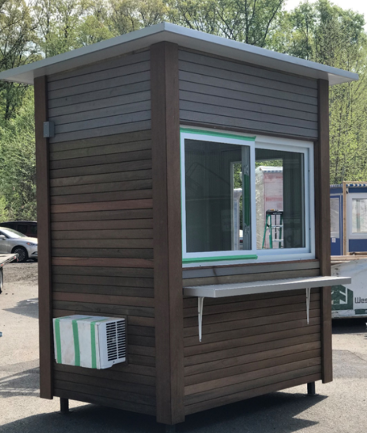 A ticket booth with brown slatted exterior and AC unit