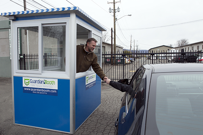 A man in a blue parking booth talking to a customer