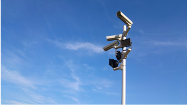 Security cameras mounted on a pole in front of blue sky