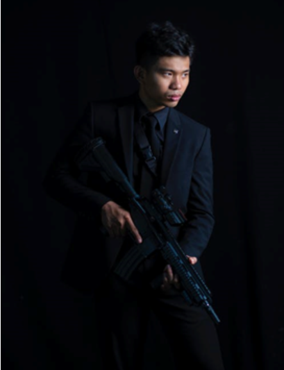 A man in a suit holding a rifle