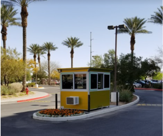 A yellow guard shack at a parking lot entrance