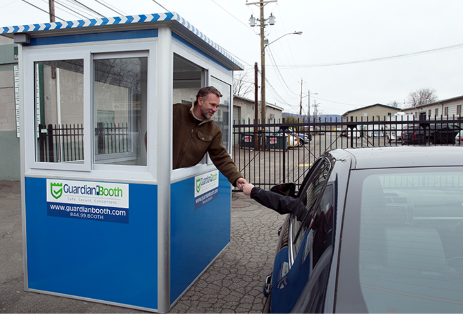 Man in a blue parking booth helping a customer in a car