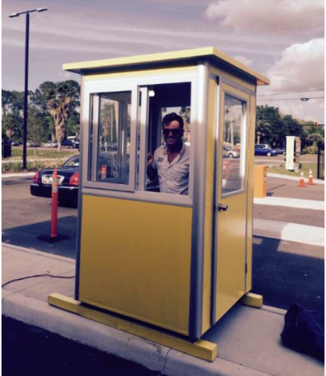 Parking attendant standing in a yellow booth