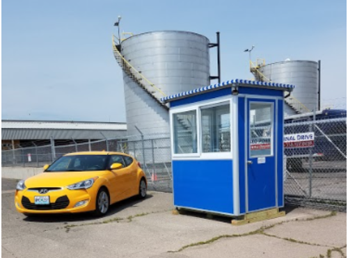 Yellow-car-parked-next-to-blue-security-booth