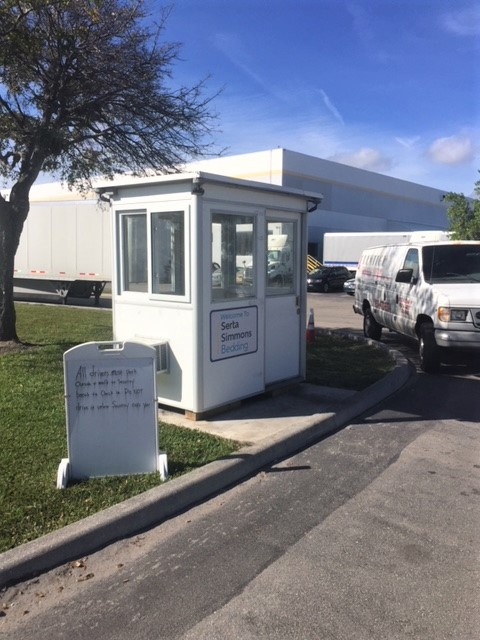 4x6 Security Guard Booth in Rivera Beach, Fl outside a warehouse with Outside Spotlights, Exterior Color Change, and Anchoring Brackets