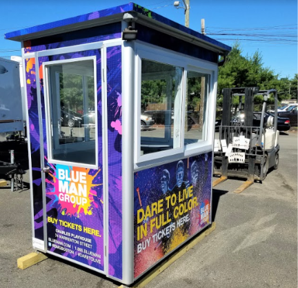 A blue and purple ticket booth with Blue Man Group signs