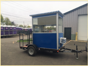 A blue booth on a trailer with big wheels