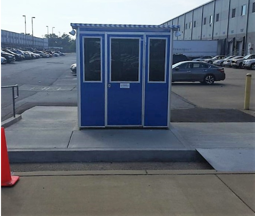 A blue guard shack in an office building parking lot
