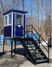 A dark blue booth at the top of an elevated platform with stairs