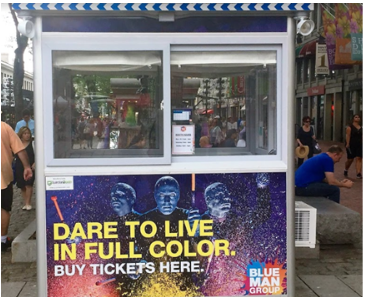 A ticket booth with Blue Man Group advertisement