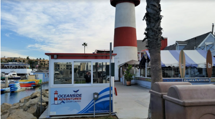 A white and red ticket booth with a lighthouse behind it