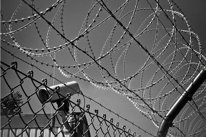 Barbed wire fence and security camera