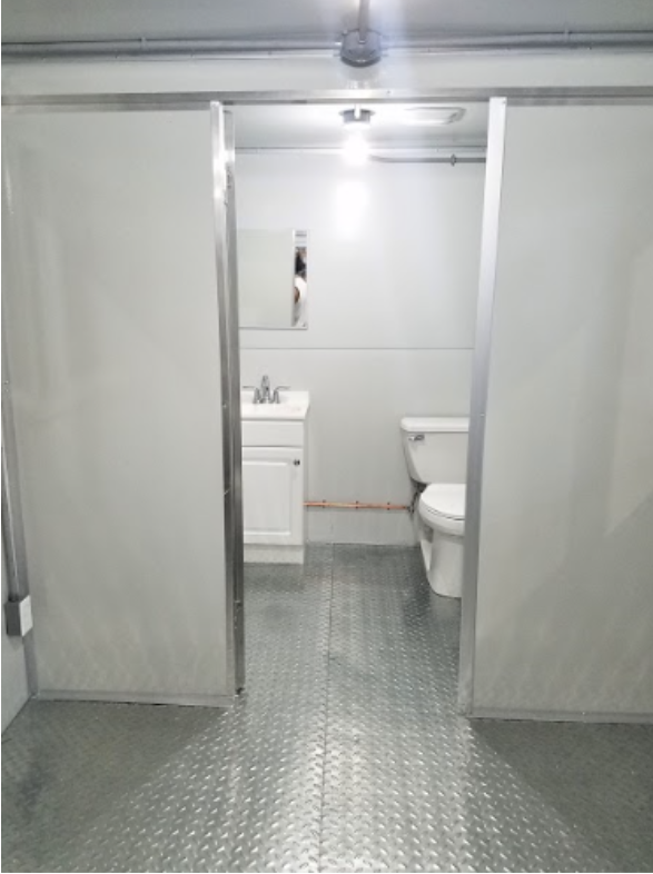 Open door showing toilet and sink with metal floor