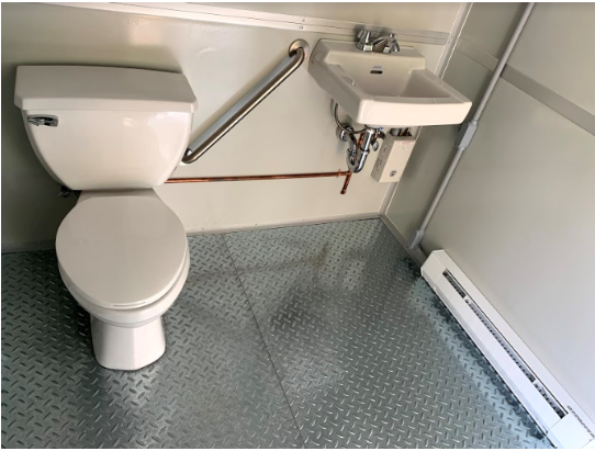 White bathroom with metal floor, white sink and toilet