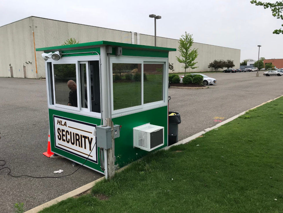 Green security booth with man running a cord to it