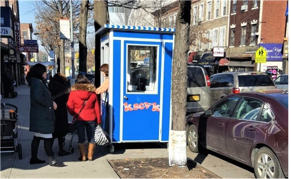 Guard booth on sidewalk with people around it