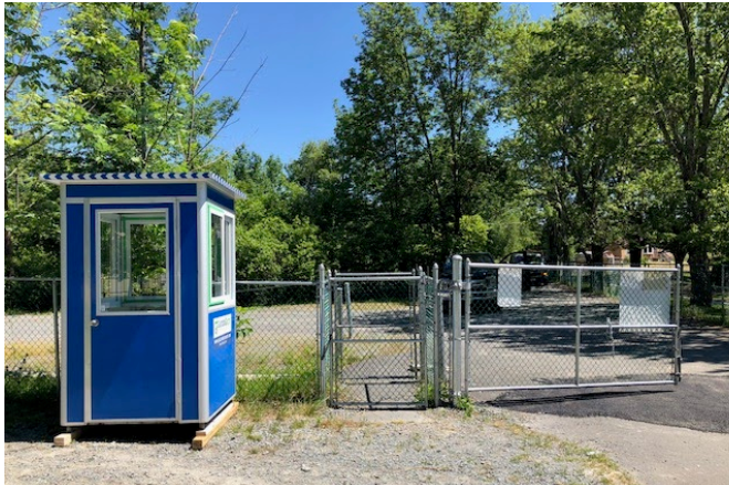 A blue guard booth outside a gate