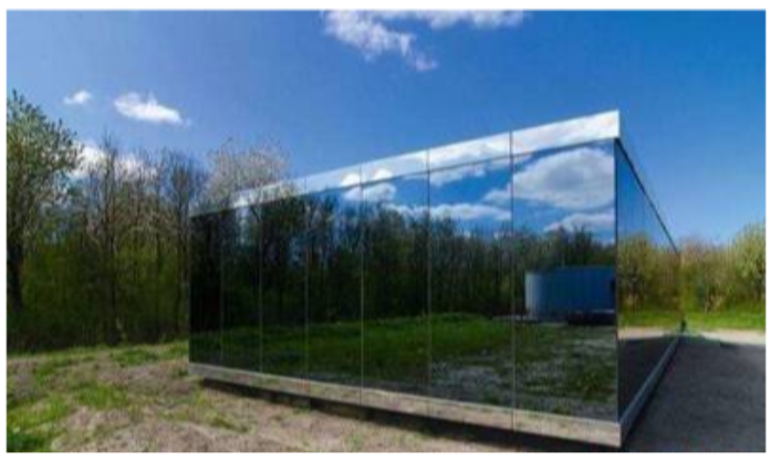 A mirrored building in the woods