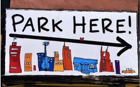 Sign that says Park Here, with cartoon buildings