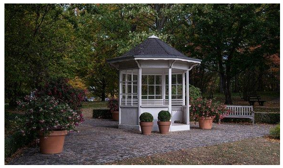 A white gazebo in a garden used as outdoor office shed