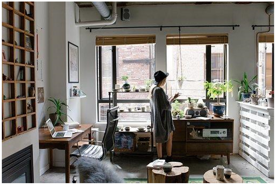 Office with windows, furniture, and a woman working