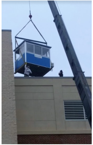A blue office booth on a crane