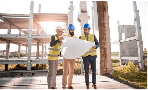Construction workers in front of a building skeleton
