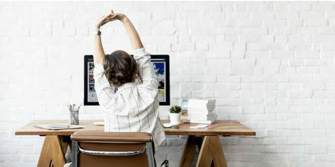Women stretching at office desk