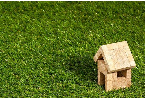 Wood toy cabin on green grass